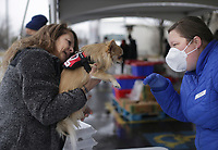 PJ Smith of Centerton (from left) shows off her dog Harley to volunteerAndrea Goucher, Thursday, January 7, 2021 at the Samaritan Community Center in Rogers. Although the building remains closed to clients and guests, Samaritan continued their drive-thru food service, providing hot meals and groceries to anyone in need. The Samaritan cafe and market served 2,235 people with groceries this week between their Springdale and Rogers locations. They distribute food every Tuesday, Wednesday and Thursday at their Rogers location from 10:30 to 12:30 and every Tuesday and Thursday at the same time at their Springdale location. Check out nwaonline.com/210108Daily/ for today's photo gallery. <br /> (NWA Democrat-Gazette/Charlie Kaijo)