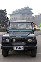 A man inside a Land Rover 50th Anniversary Limited Edtion in front of a historical city gate in Beijing, China..