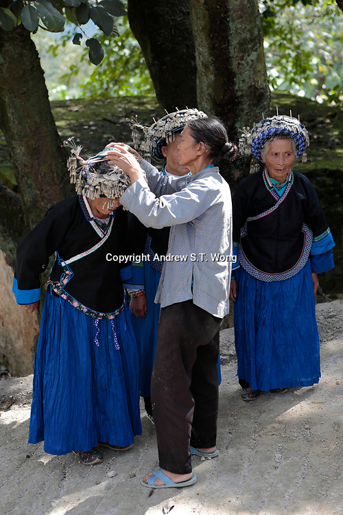 Elderly Bouyei women put on her traditional costumes at Guanling Bouyei and Miao Autonomous County in Guizhou Province, 2018.