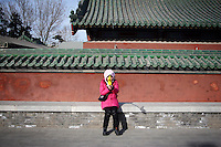 CHINA. A woman during Chinese New Year in Ditan Park in Beijing.  Chinese New Year, or Spring Festival, is the most important festival and holiday in the Chinese calendar In mainland China, many people use this holiday to visit family and friends and also visit local temples to offer prayers to their ancestors. The roots of Chinese New Year lie in combined influences from Buddhism, Taoism, Confucianism, and folk religions.  2008.