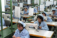 Factory workers use sewing machines at a factory in Guangzhou, China..17-JAN-03