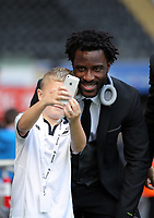 Wilfried Bony of Swansea City has a selfie taken by a young fan during the Premier League match between Swansea City and Watford at The Liberty Stadium, Swansea, Wales, UK. Saturday 23 September 2017