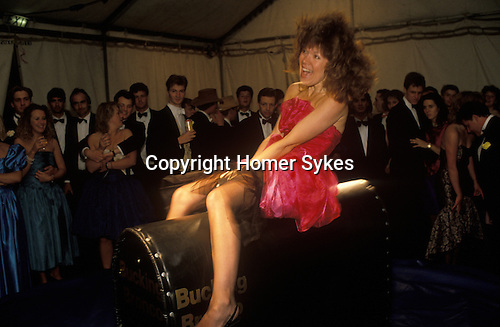 Cirencester, Gloucestershire. 1995<br /> At the Cirencester Royal Agricultural College end of year summer ball. In her short red summer party dress and sitting astride a mechanical Bucking Bronco, the fairground equivalent to a rodeo wild stallion, a young woman tries to hang on. No chance!  The many onlookers wait for her to be thrown, and inevitably lose her dignity.