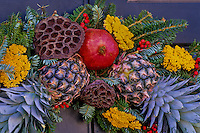 Detail of Christmas wreath using pineapples, pomegranate, yarrow, and lotus seed pods