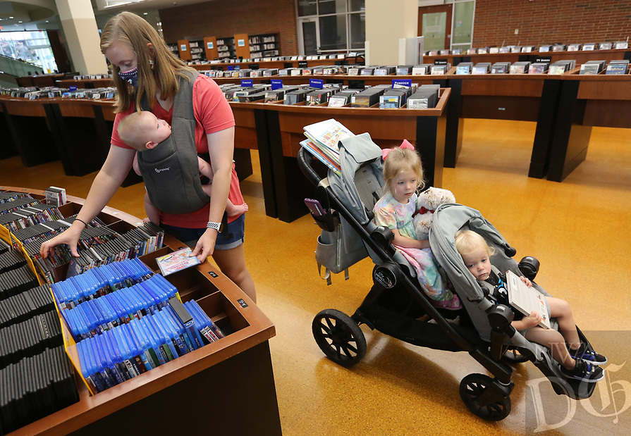 Katie Brinker (from left) looks through digital versatile disc movies Thursday, July 30, 2020, with her children Hallie, six months, Annie, 2, and Judah, 1, at the Fayetteville Public Library. The library is open with limited hours and social distancing restrictions because of the covid-19 pandemic and continues to offer online catalog items for pick-up. Check out nwaonline.com/200731Daily/ and nwadg.com/photos for a photo gallery.<br /> (NWA Democrat-Gazette/David Gottschalk)