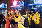 """© Joel Goodman - 07973 332324 . 16/12/2017. Manchester, UK. Three women dressed as Santa Claus huddle together for warmth as they wait for a taxi at Deansgate Locks . Revellers out in Manchester City Centre overnight during """" Mad Friday """" , named for historically being one of the busiest nights of the year for the emergency services in the UK . Photo credit : Joel Goodman"""