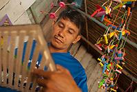 Artesão trabalha na produção dos mais variados brinquedos de miriti  como, bichos , barcos, pássaros... a fibra leve da palmeira também conhecida como Buriti e chamada de isopor da Amazônia sendo usado tradicionalmente na fabricação de artesanato vendidos durante o período do círio para pagamento de promessas ou objeto de decoração.<br /> <br /> conhecida como coqueiro-buriti, buritizeiro, miriti, muriti, muritim, muruti, palmeira-dos-brejos, carandá-guaçu e carandaí-guaçu <br /> <br /> Abaetetuba, Pará, Brasil<br /> Foto Paulo Santos