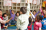 Education Preschool 3-4 year olds teacher with enthusiastic group at circle time children raising hands