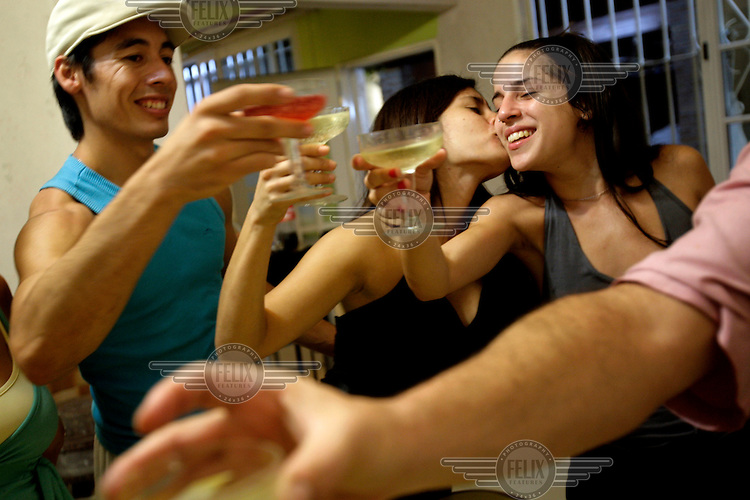 Ceci is kissed by one of her dancer friends as they toast to celebrate her birthday at her mother's house. Ceci works at a restaurant in the El Caminito area of Buenos Aires as a tango dancer.