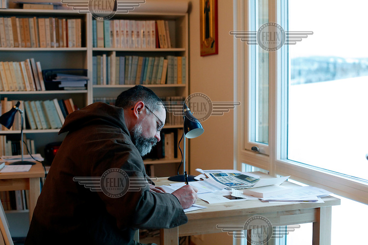 """Brother Joël writing a letter in the study. ..The new Munkeby Mariakloster - kloster is Norwegian for monastery . The four founding French monks will establish their discrete presence as a contemplative monastery according to the Rule of Saint Benedict, written in the 6th century. Brother Joel (55) & Cîteaux's Prior, brothers Arnaud (31), Bruno (33) and Cyril (81), have all chosen to be part of the founding community, despite Norway's rude climate and winter darkness at latitude 63º N, not far from the arctic circle.Munkeby, the """"place of the monks"""" was the third and northernmost Norwegian monastery established by the Cistercians in the 12th century"""