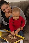 18 month old toddler boy with mother, read to, pointing at illustration in book