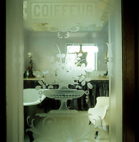 The etched glass door to this bathroom formerly graced a French hairdresser's