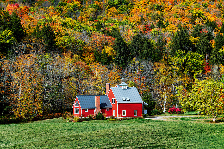 Charming red house flanked by autumn foliage.