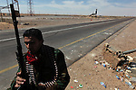 A rebel guards a checkpoint near Al Uqaylah, Libya, March, 12, 2011. The rebels continued to lose ground against loyalist forces of Col. Muammar Qaddafi and were attacked from the air, the sea and the ground.