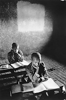 Ethiopia. West Gujam. Danbecha district. Anjeni. Anjeni is a small village. A group of pupils sit at school . They have their books open on the wood desk and listen to their teacher' s class. The walls of the classroom are made of mud. © 1996 Didier Ruef