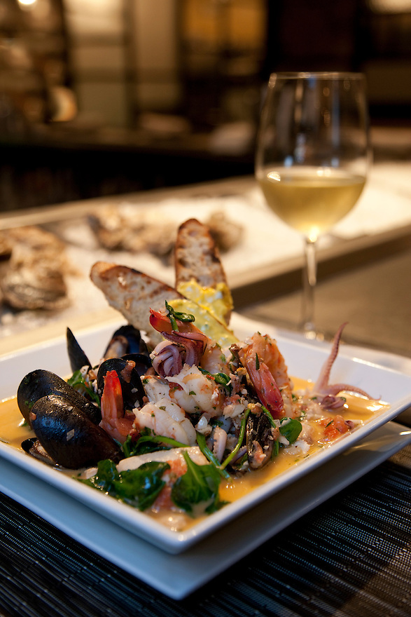 A plate of Provencale Seafood Stew at Black Salt Restaurant in Washington DC, a popular dining spot near the Potomac River in the Palisades neighborhood.