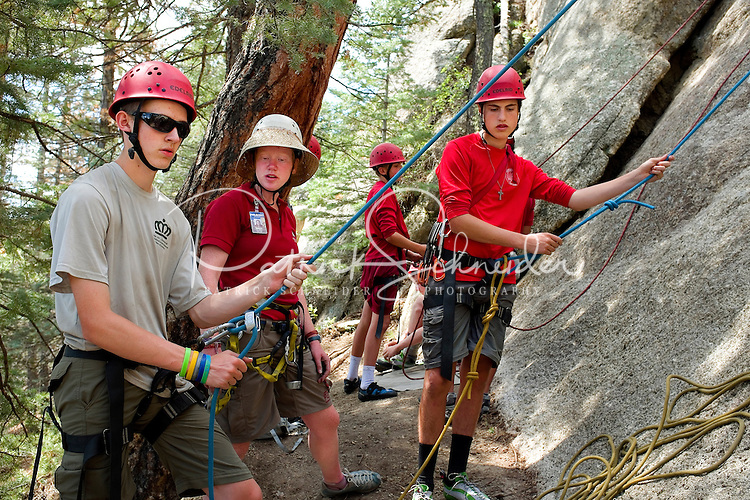 Photo story of Philmont Scout Ranch in Cimarron, New Mexico, taken during a Boy Scout Troop backpack trip in the summer of 2013. Photo is part of a comprehensive picture package which shows in-depth photography of a BSA Ventures crew on a trek. In this photo, members of the BSA Venture crew listen to instructions on proper belaying  techniques before climbing on to one of the natural rock climbing surfaces at the  Cimarroncito Camp in the backcountry at Philmont Scout Ranch.   <br /> <br /> The  Photo by travel photograph: PatrickschneiderPhoto.com