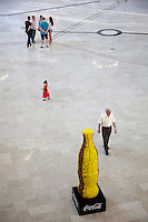 Romania. Iași County. Iasi. Town center. Palas Mall. A young girl with a red dress walks in the mall. A group of people are talking together. An elderly man with white hair and a giant yellow Cocal-Cola bottle. Coca-Cola is a carbonated soft drink sold in stores, restaurants, and vending machines throughout the world. It is produced by The Coca-Cola Company of  and is often referred to simply as Coke. Iași (also referred to as Iasi, Jassy or Iassy) is the largest city in eastern Romania and the seat of Iași County. Located in the Moldavia region, Iași has traditionally been one of the leading centres of Romanian social life. The city was the capital of the Principality of Moldavia from 1564 to 1859, then of the United Principalities from 1859 to 1862, and the capital of Romania from 1916 to 1918. 5.06.15 © 2015 Didier Ruef