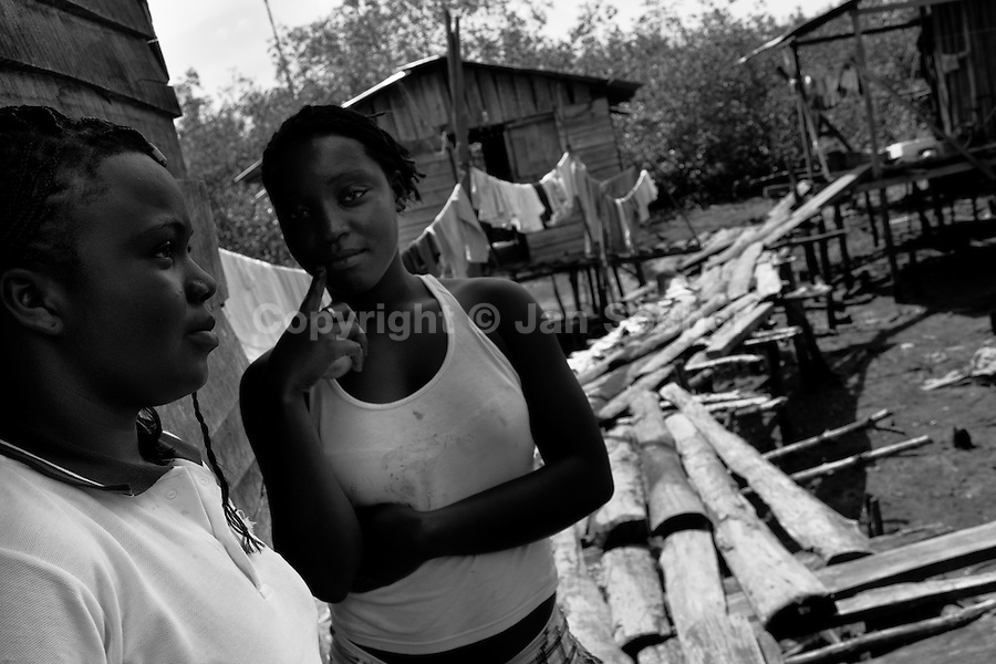 Displaced girls stand in front of a wooden house in the stilt house village close to Tumaco, Nariño dept., Colombia, 15 June 2010. With nearly fifty years of armed conflict, Colombia has the highest number of civil war refugees in the world. During the last ten years of the civil war more than 3 million people have been forced to abandon their lands and to leave their homes due to the violence. Internally displaced people (IDPs) come from remote rural areas, where most of the clashes between leftist guerrillas FARC-ELN, right-wing paramilitary groups and government forces takes place. Displaced persons flee in a hurry, carrying just personal belongings, and thus they inevitably end up in large slums of the big cities, with no hope for the future.