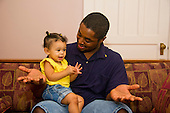 MR / Schenectady, NY. Father (22, African American) holds out his hands as he talks to his infant daughter (girl, 10 months, African American & Caucasian). MR: Dal7, Dal4. ID: AL-HD. © Ellen B. Senisi