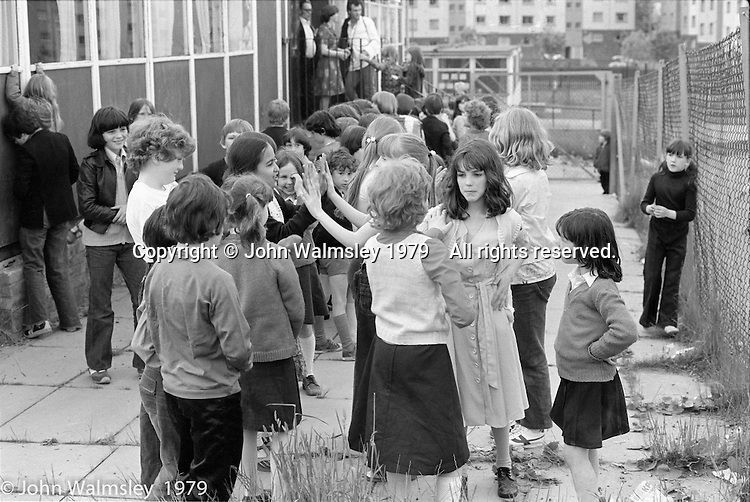 """Kids at the """"Venchie"""" (adventure playground) site, Wester Hailes, Scotland, 1979.  John Walmsley was Photographer in Residence at the Education Centre for three weeks in 1979.  The Education Centre was, at the time, Scotland's largest purpose built community High School open all day every day for all ages from primary to adults.  The town of Wester Hailes, a few miles to the south west of Edinburgh, was built in the early 1970s mostly of blocks of flats and high rises."""