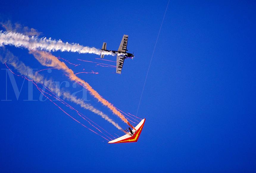 Extra 300 aerobatics plane flies through streamers trailing from wing of hang glider piloted by Dan Buchanan. Dan Buchanan. Watsonville California.