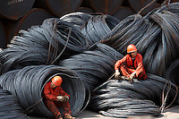 Workers take a break while sitting on a pile of steel wires at a stockyard run by the Shanghai Yirong Trading Company Ltd in Shanghai, China..10 Apr 2009
