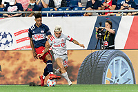 FOXBOROUGH, MA - JULY 7: Yeferson Soteldo #30 of Toronto FC brings the ball forward as Brando Bye #15 of New England Revolution defends during a game between Toronto FC and New England Revolution at Gillette Stadium on July 7, 2021 in Foxborough, Massachusetts.