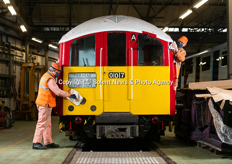 Pictured: Kieren Hetherington and Tony Long, maintenance fitters for South West Trains buff the departure board and whistle on the British Rail Class 483 Island Line train in the workshop at Ryde St Johns Road train station, Isle of Wight after its last passenger service on Sunday 3rd January 2021, ahead of being delivered to the Isle of Wight Steam Railway as the line prepares to unveil a new fleet of London Underground trains in the spring. <br /> <br /> The trains, which previously served the London Underground's Northern Line are estimated to have travelled over 3 million miles in their 82 years of service. The Island Line is currently undergoing 3 months of refurbishment ahead of unveiling a new fleet of trains, five British Rail Class 484, extensively refurbished by Vivarail.<br /> <br /> The previous two fleet service will see the train (pictured) being delivered to the Isle of Wight Steam Railway, and the other to the London Traction Transport Group with the intention of running it on the Epping Ongar Railway.<br /> <br /> In keeping with Island Line's traditions, the Class 484 trains are former London Underground trains which served on the District Line and will modernise the service on the island.<br /> <br /> © Jordan Pettitt/Solent News & Photo Agency<br /> UK +44 (0) 2380 458800