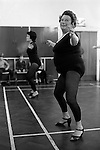 Overweight woman keeping fit exercise class wearing high heel shoes Essex England 1980s