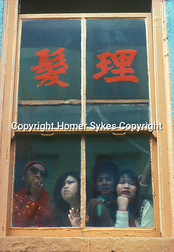 Chinese immigrant community 1970s London. Gerrard Street Chinese New Year Soho watching festival from an upstairs window 70s Uk