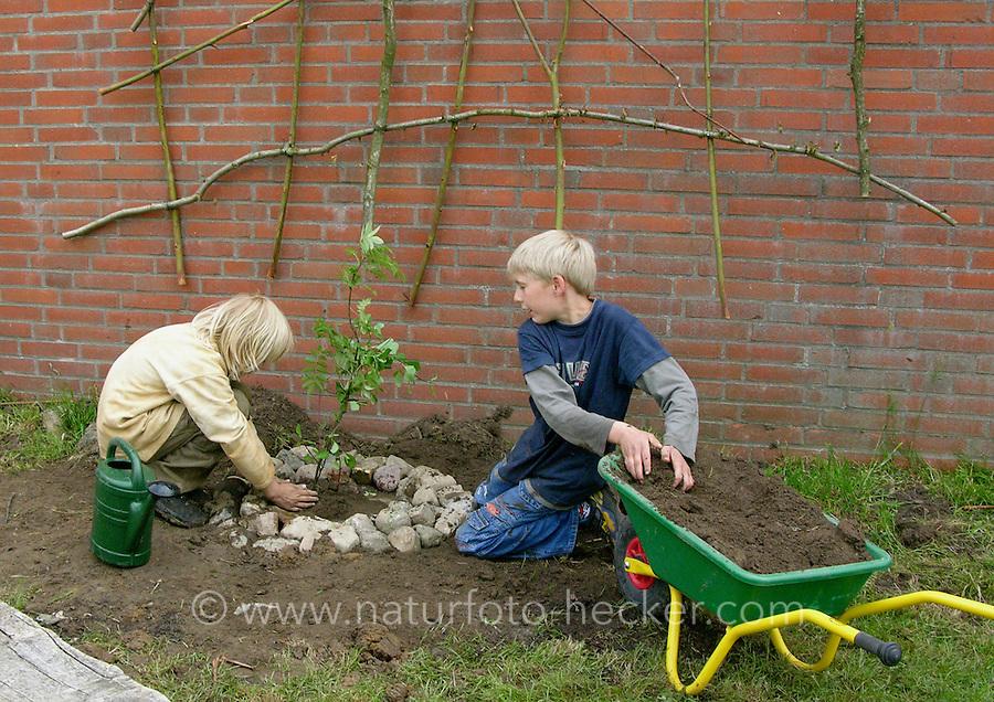 Fassadenbegrünung im Schulgarten, Begrünung einer Fassade, Garten der Grundschule Nusse wird als Projektarbeit von einer 1. Klasse gestaltet, Kinder pflanzen Rankpflanzen an selbstgebaute Kletterhilfen, Gartenarbeit
