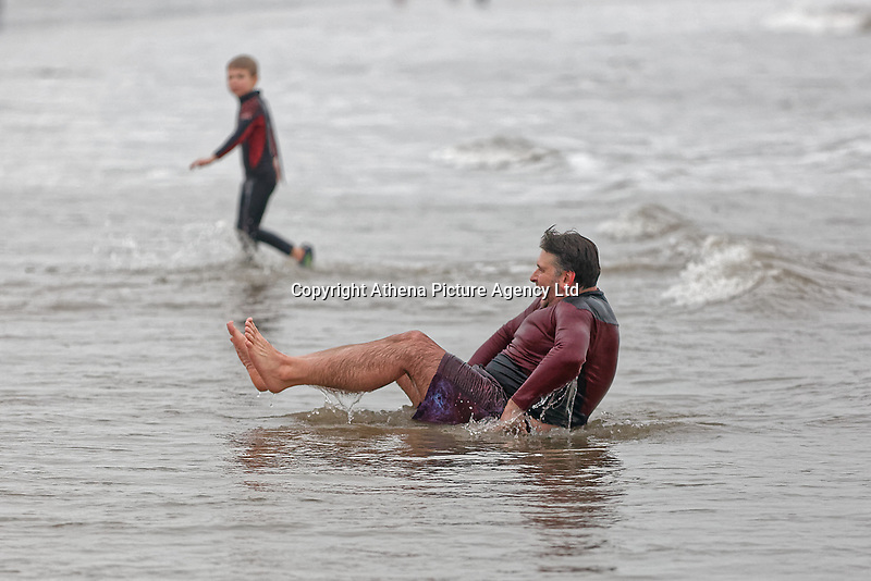Pictured: A man attempts to get back onto his feet. Tuesday 25 December 2018<br /> Re: Hundreds of people take part in this year's Porthcawl Christmas Swim in south Wales, UK.