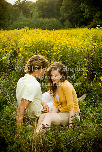 Couple sitting together in open field of tall grasses
