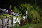 Bamber Bridge 1 Radcliffe 1, 07/09/2021. Sir Tom Finney Stadium, Northern Premier League Premier Division. A man standing in his garden overlooking the pitch watches the second-half action as Bamber Bridge take on Radcliffe in a Northern Premier League Premier Division fixture at the Sir Tom Finney Stadium, named after the late England international player who was born locally. Formed in 1952, Bamber Bridge, which is owned by a community organisation, merged with Walton-le-Dale FC in 1974 and moved to their current ground in 1983. The match against their opponents from Greater Manchester ended in a 1-1 draw, with Radcliffe missing a late penalty, watched by 393 spectators. Photo by Colin McPherson.