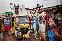 """Nigeria. Enugu State. Enugu. Town center. An elderly Igbo woman stands close to a yellow auto rickshaw used by """"Keke"""" drivers for transporting people around town. The  tricycle better known in Nigeria as the Keke NAPEP is gaining the dominance on Nigerian roads sweeping every street of cities and villages. The auto rickshaw is a common form of urban transport, both as a vehicle for hire and for private use. The old woman is wearing a head tie which is a women's cloth head scarf. The head tie is used as an ornamental head covering or fashion accessory, or for functionality in different settings. Its use or meaning can vary depending on the country and/or religion of those who wear it. The head tie is called gele in Nigeria. Catholic religious symbols. Plaster statues of the crucifixion of Jesus, Jesus Blessing and the Virgin Mary. Collectively referred to as the Passion, Jesus' suffering and redemptive death by crucifixion are the central aspects of Christian theology concerning the doctrines of salvation and atonement. Enugu is the capital of Enugu State, located in southeastern Nigeria.  28.06.19 © 2019 Didier Ruef"""