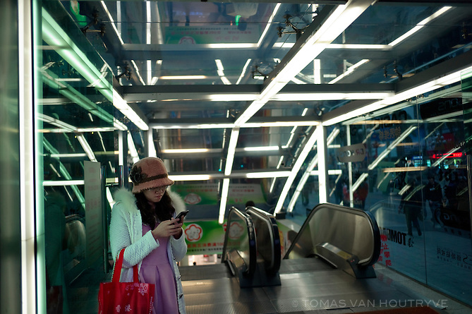 A woman checks her phone at the exit of a shopping center on Huanqiang Road in Shenzhen, China on Feb. 8 2012. The shopping district is crammed with electronic stores where one can buy anything from fake iPhones to flat screen televisions.