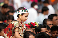 A Bangladeshi child sits on the shoulder of her father as they along with others stand in a queue to pay homage at the Dhaka Central Shaheed Minar, or Martyr's Monuments on International Mother Language Day in Dhaka, Bangladesh, Saterday, Feb. 21, 2015. I