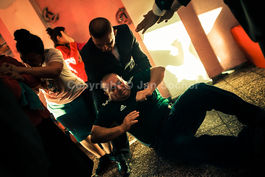 A Christian follower, a member of a local religious cult, falls to the ground during the religious trance in a home church in San Salvador, El Salvador, 25 November 2018. A small community of believers gathers every week in an unmarked home church to carry out prayers of liberation, invocations and the so-called evil expulsion rites. Reciting religious formulas through very loud speakers, using manipulative verbal techniques, intimidation and intense charisma, the leading pastor commands the supposed evil spirits to depart a devotee's mind and body which should bring to a devotee a spiritual relief.