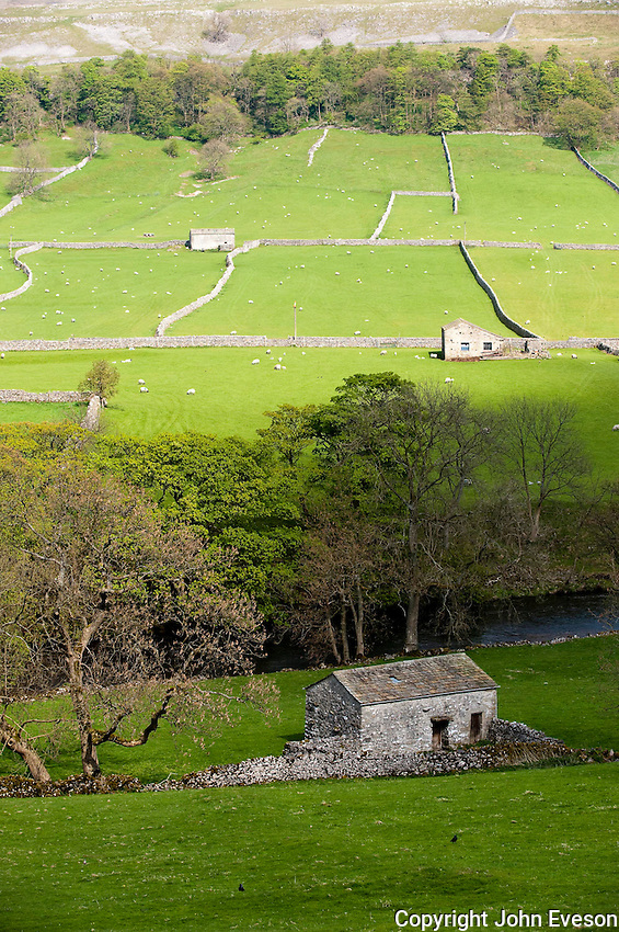 Stone barn, Kettlewell, North Yorkshire with stone wall in front of river Wharfe.
