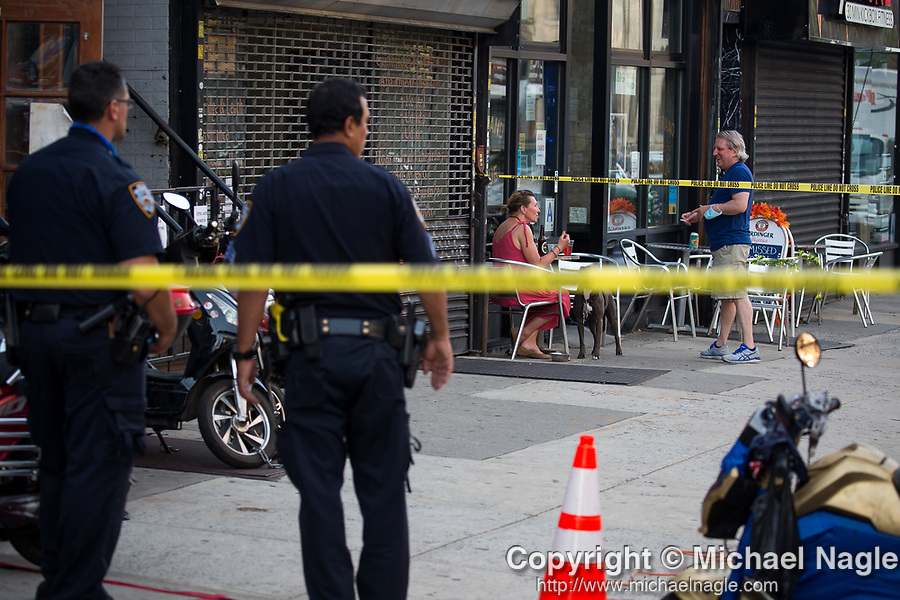 People sit in front of the Nostrand Avenue Pub as the NYPD investigates a homicide one store over at Fly E-Bike at 662 Nostrand Avenue on July 18, 2020 in the Crown Heights neighborhood of the Brooklyn borough of New York City.  The 23 year-old victim, who died at Kings County, was shot in the leg and stomach.  Photograph by Michael Nagle