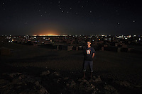 Azmah Laulad, 18. Pictured in Auserd refugee camp, Algeria, with the lights of Tindouf in the background: 'I've grown up in Auserd but I don't like it. When I was ten we were travelling in the desert and the truck broke down. We were stuck there for six days and had to drink water from the radiator. There was a pregnant woman with us and everyone thought she would lose the baby but it was lucky, a car came along and we fixed the truck. Now I'm making bricks and soon me and my brother will build a shop. We will sell mobile phones because there are not enough phone shops here. It's a tragedy here, people need to go back.' .