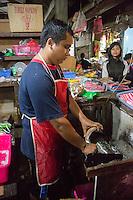 Bali, Indonesia.  Young Man Shredding Fresh Coconut.  Jimbaran Market.