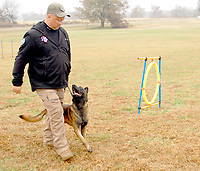 Marc Hayot/Herald Leader Owner Rob Shewmake and Pike demonstrate obedience techniques.