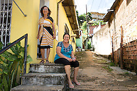 2 woman sit on the entrance to their house watching the fans walk past