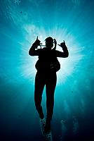 silhouette of diver in a sunburst. Maui, Hawaii