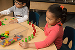 Education preschool 3-4 year olds girl setting up dominos on table, boy working on puzzle nearby