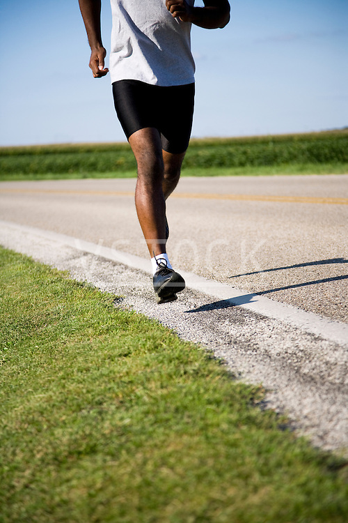 USA, Illinois, Metamora, man jogging down country road