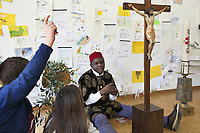 Switzerland. Canton Ticino. Barbengo. Elementary school. Don Gerald Chukwudi Ani is a catholic priest from Nigeria. He teaches religions' history to children. Wearing a boubou printed with lion's heads and a red hat, he sits on the floor. His two legs surround a crucifix one meter in height. He has on his left a paschal candle which will be lit on the occasion of the solemn celebrations of the Easter vigil, to mark the expectation of the resurrection of Christ. On his right, placed on a chair, olive branches recall the triumphal entry of Jesus into Jerusalem under the cheering of the crowd waving palms. Drawings on the wall. Barbengo is a quarter of the city of Lugano. 23.03.2018 © 2018 Didier Ruef