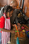 Father in kitchen with 8 year old daughter, food preparation, making salad, girl peeling carrot, talking